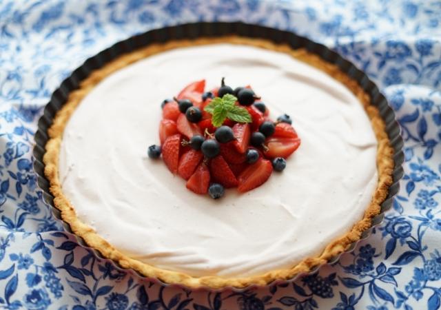 Vychlazený bezlepkový jahodový koláč ozdobený sezónním ovocem
